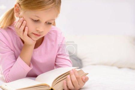 Photo pour Un roman intéressant. Jolie petite fille heureuse tenant le livre et le lisant tout en étant allongé sur le canapé - image libre de droit