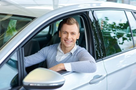 Photo for Confident driver. Delighted cheerful smiling man sitting in the car while going to buy it - Royalty Free Image