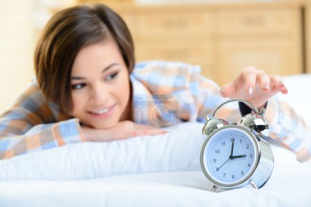 Young girl touching the alarm clock.