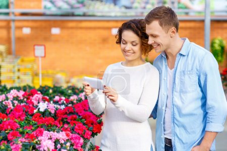 Couple taking pictures of blooming flowers.