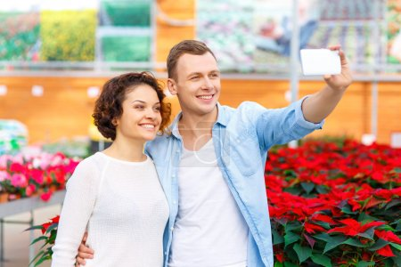 Young couple taking selfies at orangery.