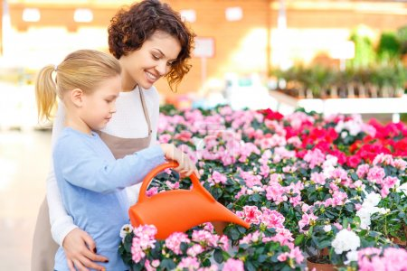 Little girl and florist watering flowers.