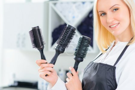 Hairdresser holding several hairbrushes.