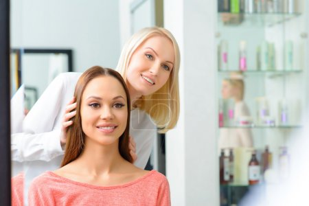 Stylist is showing hairdo to her client.