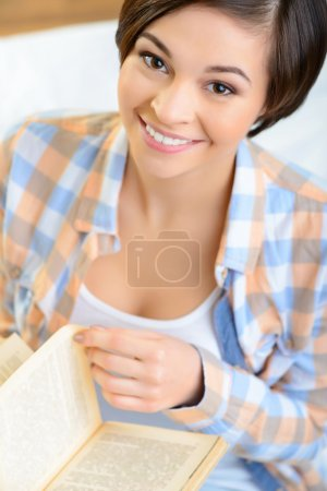 Smiling teenage girl is reading a book.