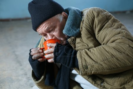 Homeless man hungrily drinking water.