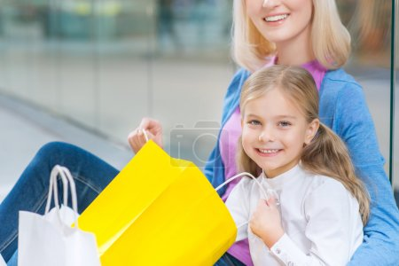 Photo for Live colorful. Close up of pretty little girl opening package and having shopping with her mother while sitting on the floor - Royalty Free Image