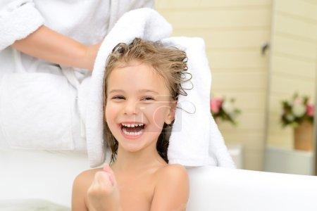 Photo pour Plein de positivité. Joyeuse petite fille assise dans le tube de bain tandis que sa mère pendant ses cheveux avec une serviette - image libre de droit