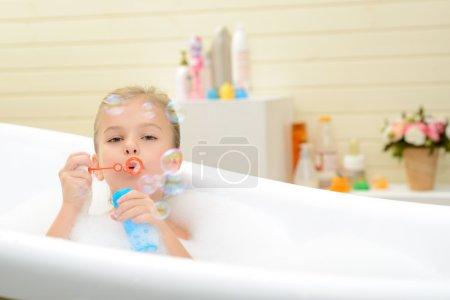 Photo pour Enfance heureuse. Agréable petite fille espiègle soufflant des bulles de savon et de s'amuser tout en prenant bain - image libre de droit