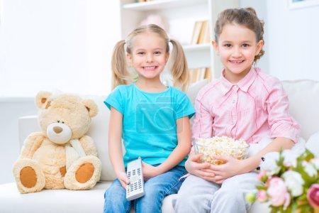 Photo pour Plein de positivité. joyeuses petites sœurs souriantes assises sur le canapé et regardant la télévision tout en exprimant leur joie - image libre de droit