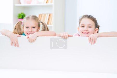 Photo pour Plein de positivité. Petites sœurs souriantes gaies se cachant derrière le canapé et se sentant ravies tout en s'amusant à la maison - image libre de droit