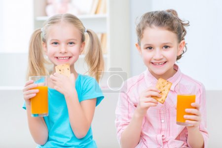 Photo for Take some energy. Pleasant smiling little sisters eating snack and drinking juice while feeling happy - Royalty Free Image