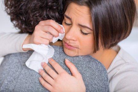 Photo pour Se sentir triste. Jeune femme jolie est étreindre sa sœur tout en pleurant malheureusement - image libre de droit