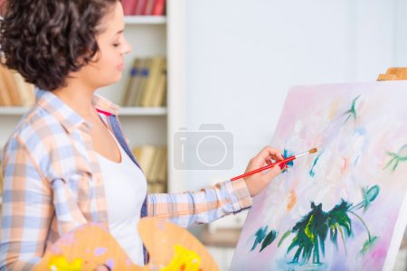 Young woman is painting a nature mort.