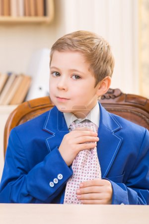 Little boy adjusting big tie.