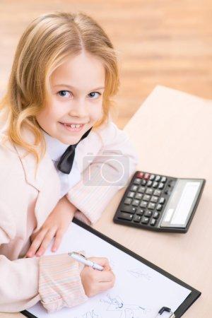 Photo pour Temps de tirage. Petite fille sourit tout en étant assise au bureau et en dessinant - image libre de droit