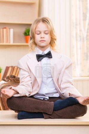 Little girl is meditating on the desk.