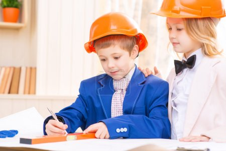 Little girl and boy are working with construction papers.