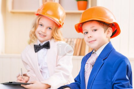 Photo for Little professionals. Boy and girl are smiling while wearing orange protective helmets - Royalty Free Image