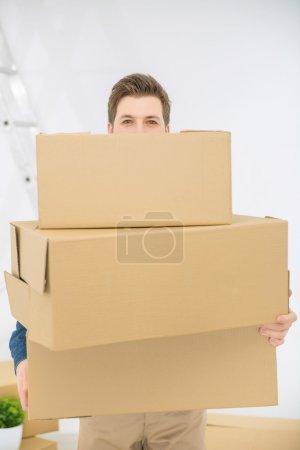 Photo pour Plein de positivité. Gros plan d'un homme souriant et joyeux tenant des boîtes et se tenant debout dans une pièce tout en étant impliqué dans l'enlèvement - image libre de droit