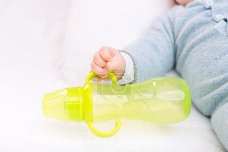 Photo pour Je prends une bouteille. Petit bambin attrapant sa bouteille jaune - image libre de droit