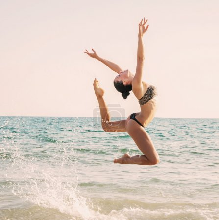 Photograph of a beautiful female dancer jumping  on a beach in t