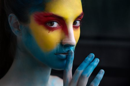 Painted beautiful woman face, artistic make up, body and face art
