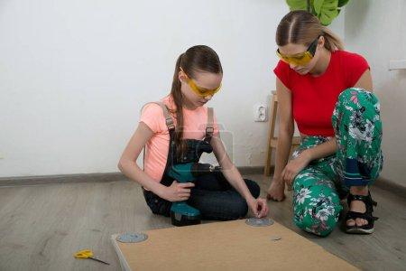 Photo pour Deux filles avec des outils réparer des meubles sur le sol dans la chambre. Petite fille et jeune femme font leurs devoirs. Professions et carrière. Choix féminin. - image libre de droit