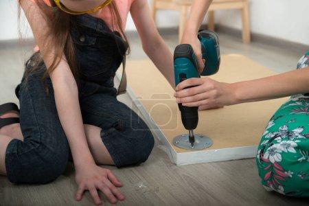 Photo pour Les filles mains avec des outils de tournevis réparer les meubles sur le sol dans la chambre. Petite fille et jeune femme font leurs devoirs. Professions et carrière. Choix féminin. - image libre de droit