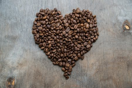 Photo pour Gros plan des grains de café dans une assiette vintage argentée sur fond en bois - image libre de droit