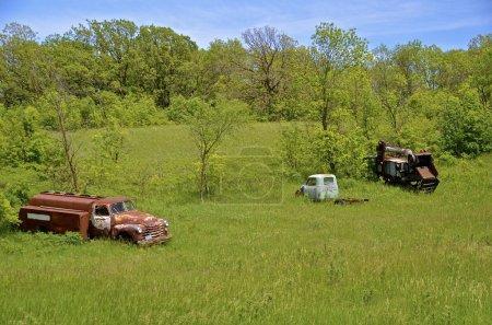 Photo pour Garé sur le bord d'une forêt est une ancienne batteuse, un camion-citerne et un pick-up 1 tonne. - image libre de droit