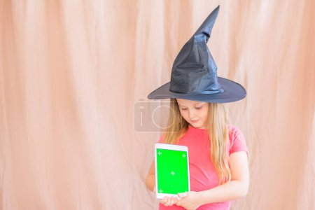 Photo for Beautiful positive little girl 6 years old in a witch hat on an isolated background holds a tablet with a green mocap screen and looks at the camera. Concept: celebrating halloween using gadgets mocap - Royalty Free Image