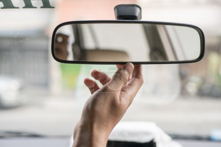 woman adjusting rear view mirror