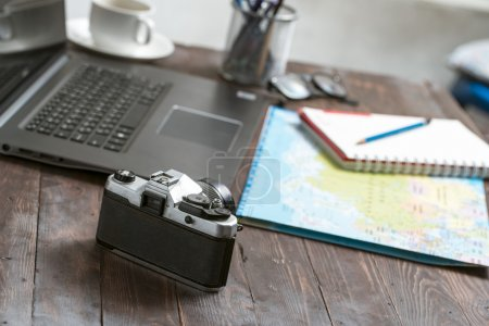 Dress travelers with a camera. Notebook on the wooden floor vint