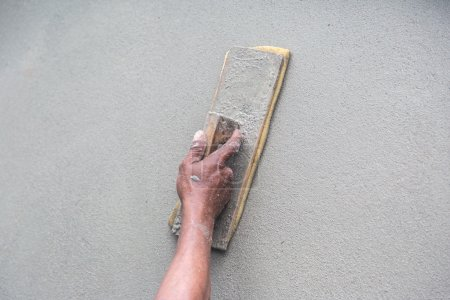 Man's hand plastering a wall with trowel. Construction worker. M