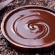 Bowl of melted chocolate and wooden spoon on a cru...