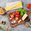 Italian food background with vine tomatoes, basil, spaghetti, olives, parmesan, olive oil, garlic Ingredients on stone table and cutting board Copy space Top view