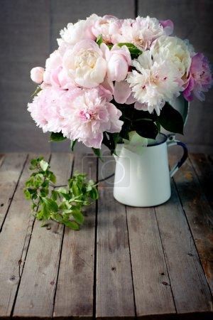 Photo pour Bouquet de fleurs de pivoine vert feuilles dans un bocal d'émail sur un fond en bois - image libre de droit
