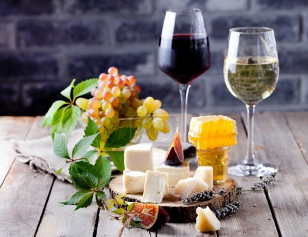Cheese plate with honey, nuts and grape and white ...