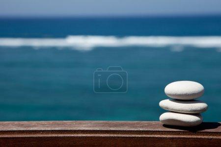 Photo pour Pile de pierres de galets sur la plage, sur une surface en bois - image libre de droit