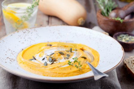 Pumpkin soup with cream, seeds and thyme