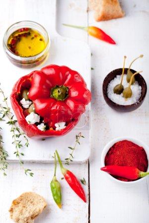 Foto de Pimientos rellenos al horno relleno con queso, tomates, hierbas, alcaparras y anchoas sobre un fondo blanco de madera - Imagen libre de derechos