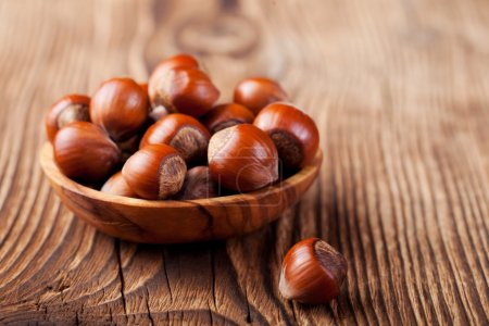 Hazelnuts in a wooden bowl. Wooden background.