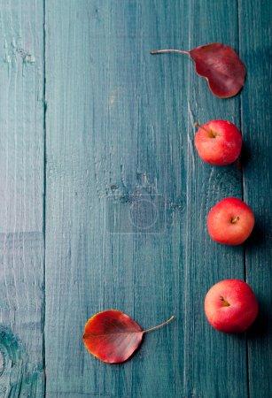 Photo pour Pommes rouges et feuilles sur fond bleu bois, turquoise - image libre de droit