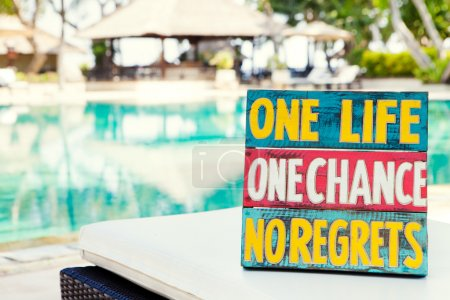 Foto de Inspirational Motivational Life Quote wooden board One Life One Chance No regrets on summer, tropical swimming pool background Copy space - Imagen libre de derechos