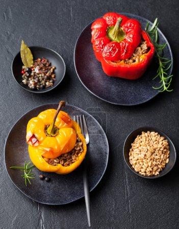 Foto de Pimientos rellenos al horno relleno con trigo espelta, arroz, vegetales sobre un fondo de piedra oscuro placa - Imagen libre de derechos