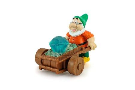 Grumpy character form 7 Dwarfs pushing wheelbarrow with a diamon