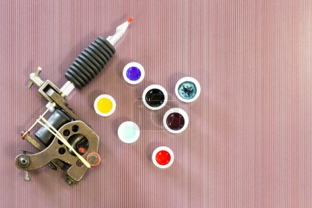 Photo for Background of a tattoo session consists in a tattoo machine and ink cups colored - Royalty Free Image
