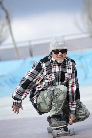Photo pour Gros plan d'un patineur vieil homme skate accroupi avec sa planche à roulettes sur un parc de patinage - se concentrer sur le visage - image libre de droit