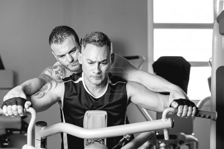 personal trainer helping man with shoulder exercise
